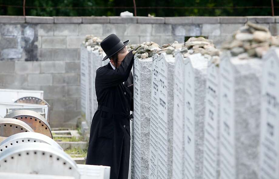 A man prays near the mausoleum during the annual observance of the 1979 death of Rabbi Joel Teitelbaum at the Satmar Cemetery #2 in Kiryas Joel, N.Y. on Friday, Aug. 2, 2013. Thousands of Satmar Hasidim and Orthodox Jews are expected to stream into Kiryas Joel today for annual observance of the 1979 death of Rabbi Joel Teitelbaum, founder of the Satmar Hasidic movement and namesake of the Orange County village. (AP Photo/Times Herald-Record, Chet Gordon) Photo: Chet Gordon, Associated Press