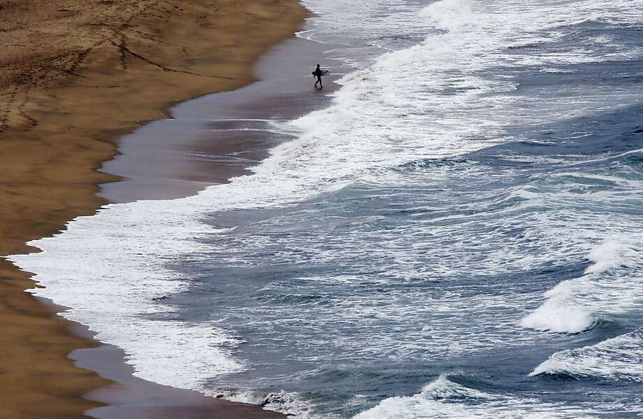 A surfer enters the water at Montara State Beach on Friday, Aug. 2, 2013, in Montara, Calif. (AP Photo/Marcio Jose Sanchez) Photo: Marcio Jose Sanchez, Associated Press
