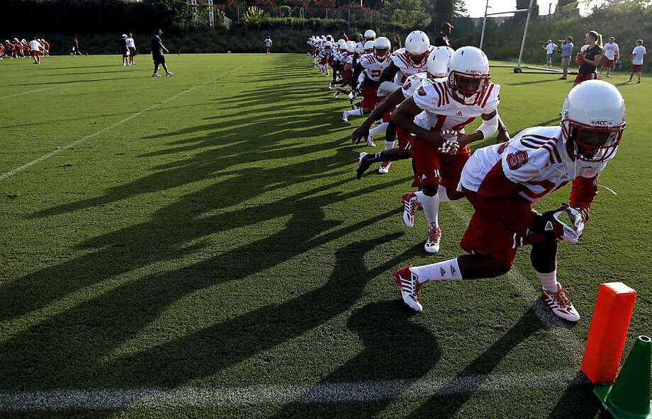 North Carolina State players run through drills during the team's first NCAA college football practice of the season in Raleigh, N.C., Friday, Aug. 2, 2013. (AP Photo/Gerry Broome) Photo: Gerry Broome, Associated Press
