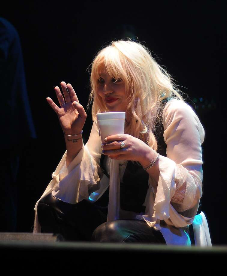 Love downs a shot of tequila during her show. Photo: Dave Rossman, For The Houston Chronicle