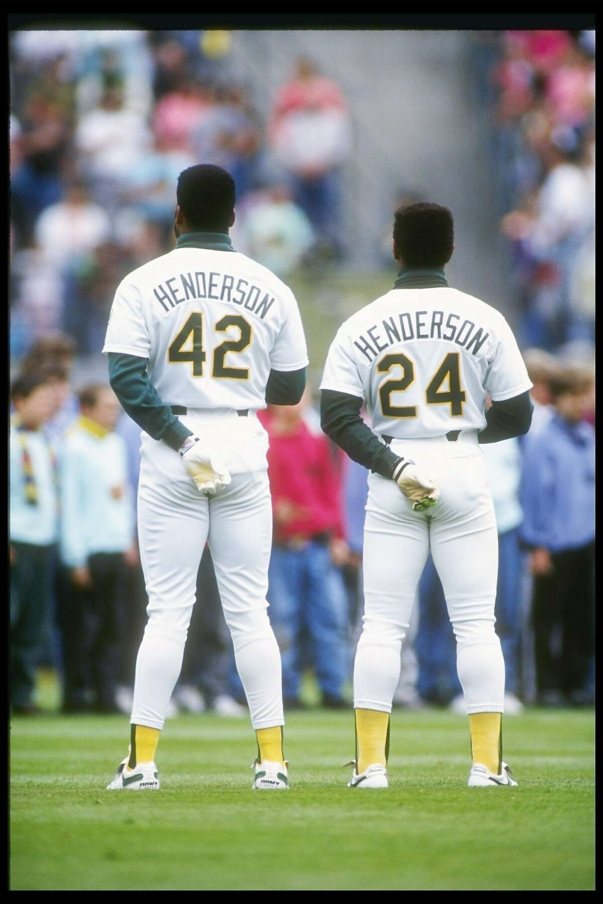1991: Outfielders Dave Henderson (left) and Rickey Henderson of the Oakland Athletics stand with backs to camera.