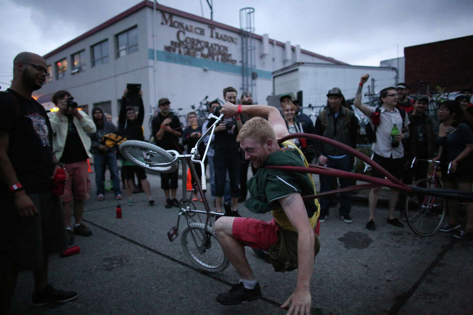 Chris Pavelek is pulled off his bike while participating in bike slingshot. Photo: JOSHUA TRUJILLO, SEATTLEPI.COM / SEATTLEPI.COM