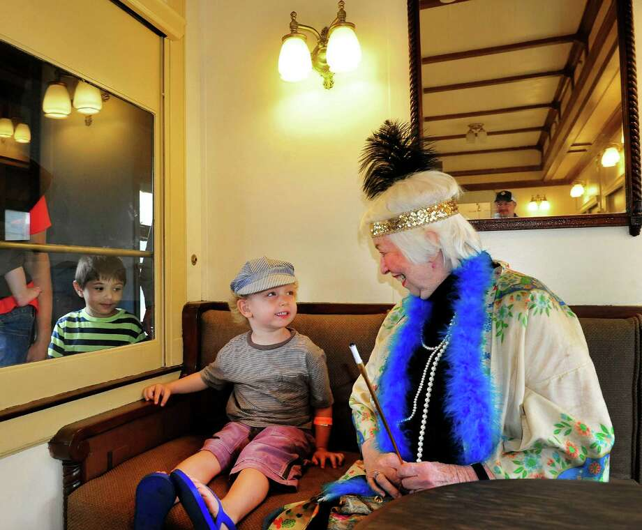 David Matulis, 3, center, listens to Terrie Roese, who is dressed in the period costume of 1928, when the 20th Century Limited observation car they are in was built, during Danbury Railway Day at the Danbury Railway Museum, Saturday Aug. 3, 2013, in Danbury, Conn. Photo: Michael Duffy / The News-Times