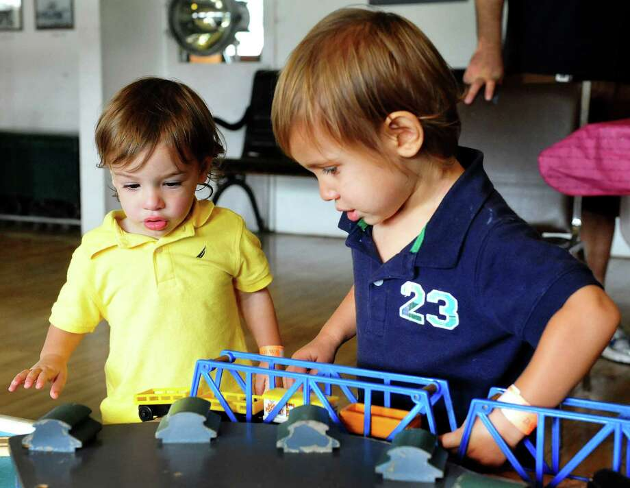 Alessandro Romaro, 1, left, and his brother, Lorenzo, 2, of New Milford, play with trains during Danbury Railway Day at the Danbury Railway Museum, Saturday Aug. 3, 2013, in Danbury, Conn. Photo: Michael Duffy / The News-Times