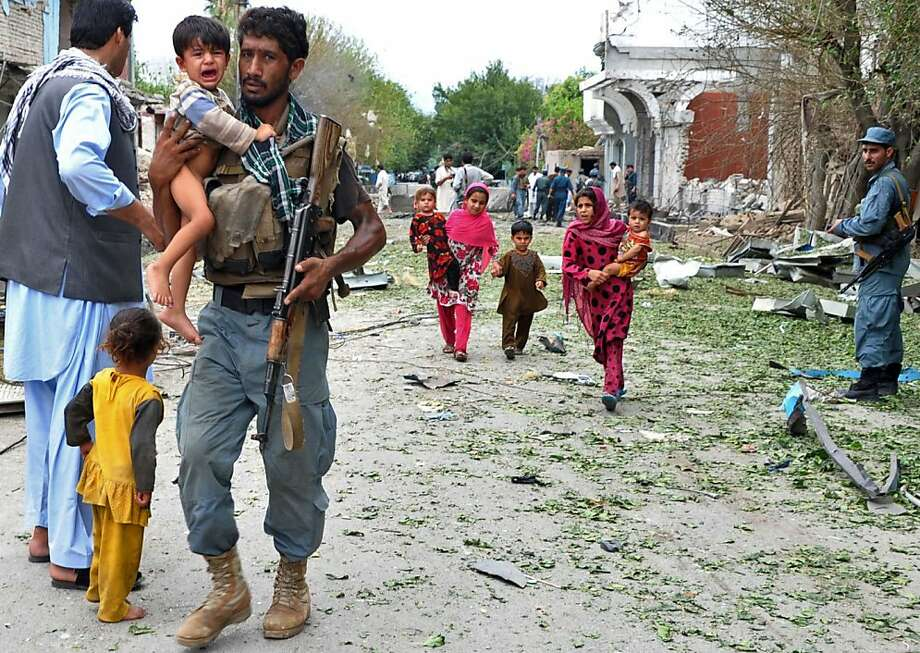 A policeman carries a child at the site of a suicide attack in Jalalabad. Photo: Noorullah Shirzada, AFP/Getty Images
