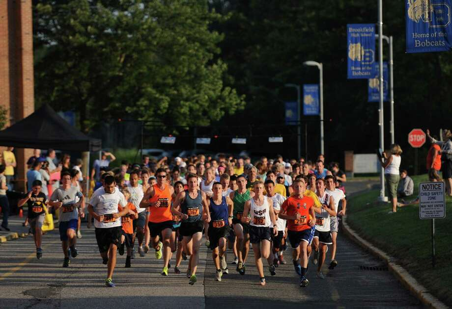 Runners take of from the starting line at the First Annual Sunset Sizzler 5K at Brookfield High School in Brookfield, Conn. on Friday, Aug. 2, 2013.  230 runners and walkers participated in the event, raising money for Brookfield High School athletics.  Parker Timmerman, 17, of Brookfield, finished first overall with a time of 16:12, and Rose Willey, 20, of Brookfield, was the first female finisher with a time of 19:08. Photo: Tyler Sizemore / The News-Times