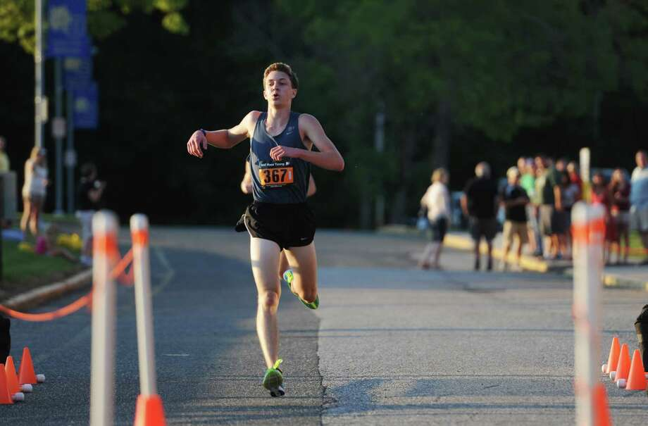 Overall winner Parker Timmerman, 17, of Brookfield, crosses the finish line with a time of 16:12 in the First Annual Sunset Sizzler 5K at Brookfield High School in Brookfield, Conn. on Friday, Aug. 2, 2013.  230 runners and walkers participated in the event, raising money for Brookfield High School athletics. Rose Willey, 20, of Brookfield, was the first female finisher with a time of 19:08. Photo: Tyler Sizemore / The News-Times
