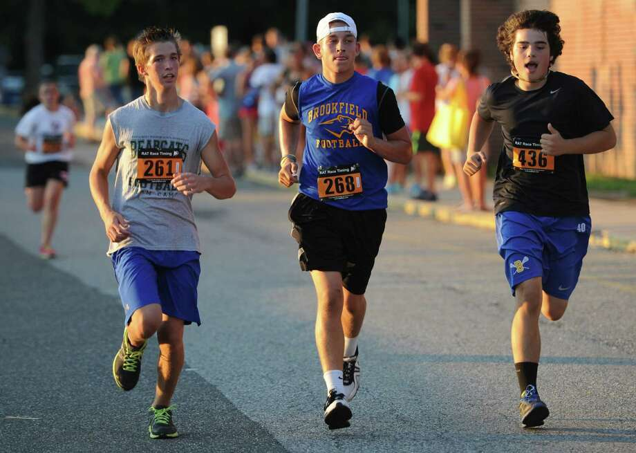 From left, Caleb Wardenburg, 14, Brad Westmark, 17, and Dane Borges, 14, of Brookfield, sprint to the finish of the First Annual Sunset Sizzler 5K at Brookfield High School in Brookfield, Conn. on Friday, Aug. 2, 2013.  230 runners and walkers participated in the event, raising money for Brookfield High School athletics.  Parker Timmerman, 17, of Brookfield, finished first overall with a time of 16:12, and Rose Willey, 20, of Brookfield, was the first female finisher with a time of 19:08. Photo: Tyler Sizemore / The News-Times