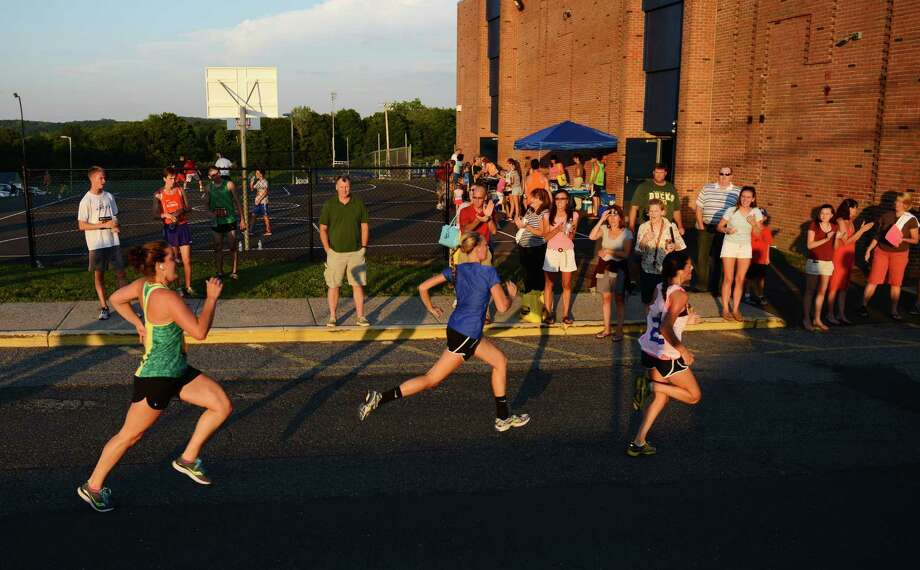 A group of runners sprints to the finish line at the First Annual Sunset Sizzler 5K at Brookfield High School in Brookfield, Conn. on Friday, Aug. 2, 2013.  230 runners and walkers participated in the event, raising money for Brookfield High School athletics.  Parker Timmerman, 17, of Brookfield, finished first overall with a time of 16:12, and Rose Willey, 20, of Brookfield, was the first female finisher with a time of 19:08. Photo: Tyler Sizemore / The News-Times