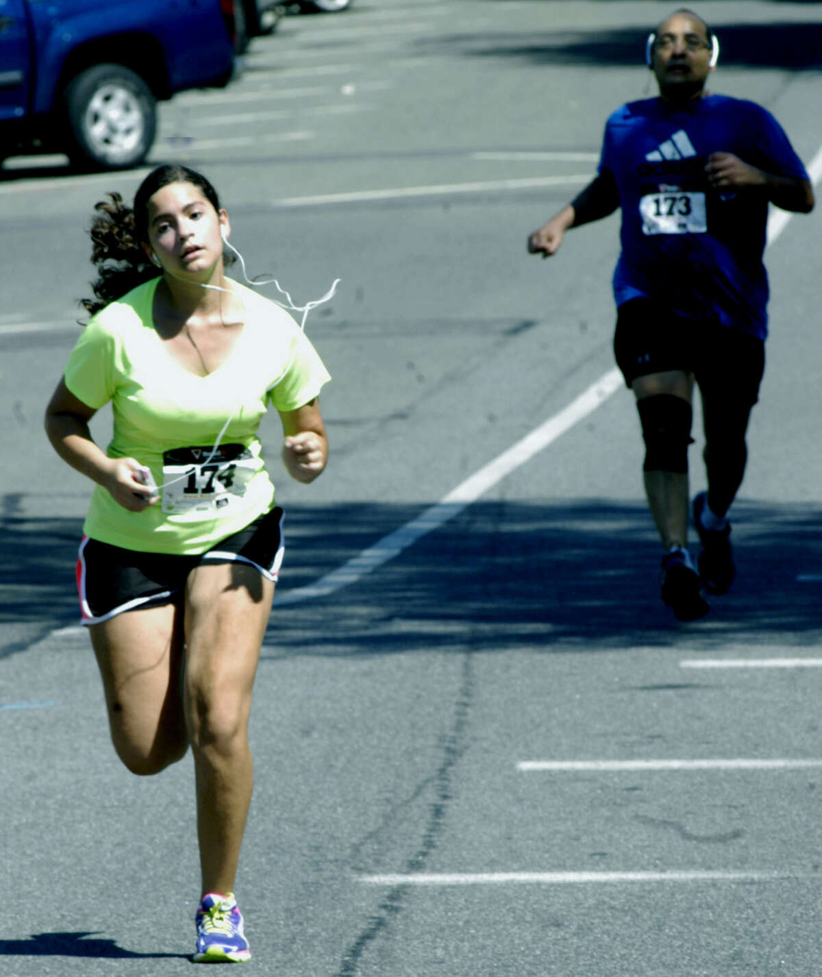 Christina Khalil, 13, of New Miford engages in a spirited battle with Magdi Khalil, 47, of New Milford during the stretch run for the 46th annual New Milford 8-mile road race July 27, 2013