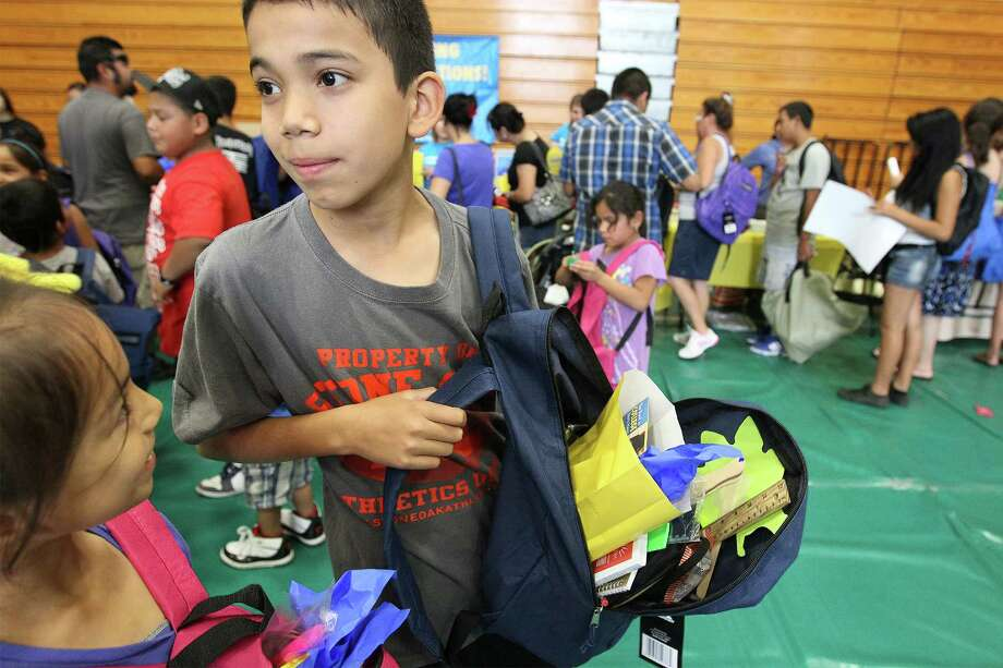 Alejandro Castoreno, 10, shows his backpack filled with various school supplies at a back to school event hosted by State Senator Carlos Uresti at Palo Alto College on Saturday, Aug. 3, 2013. People gathered in line as early as two hours before the event started to supply their children with backpacks and school supplies. Along with school supplies, the San Antonio Food Bank was also on hand to give out boxes of food to the recipients. Sen. Uresti hosts these giveaways in all areas of his district which is the third poorest in Texas according to the state senator. Uresti provides the supplies through private and corporate donors as well as his own contribution. Photo: Kin Man Hui, San Antonio Express-News / ©2013 San Antonio Express-News