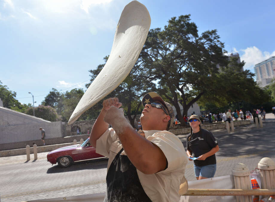 "Alex Rymers of Dirt Road Cookers tosses dough in front of the Guinness museum during an attempt to snag the Guinness World Record for the ""largest commercially available"" pizza on Saturday, Aug. 3, 2013. The pizza was 92 1/2 inches in diameter and weighed about 88 lbs. Photo: Robin Jerstad, For The San Antonio Express-News"