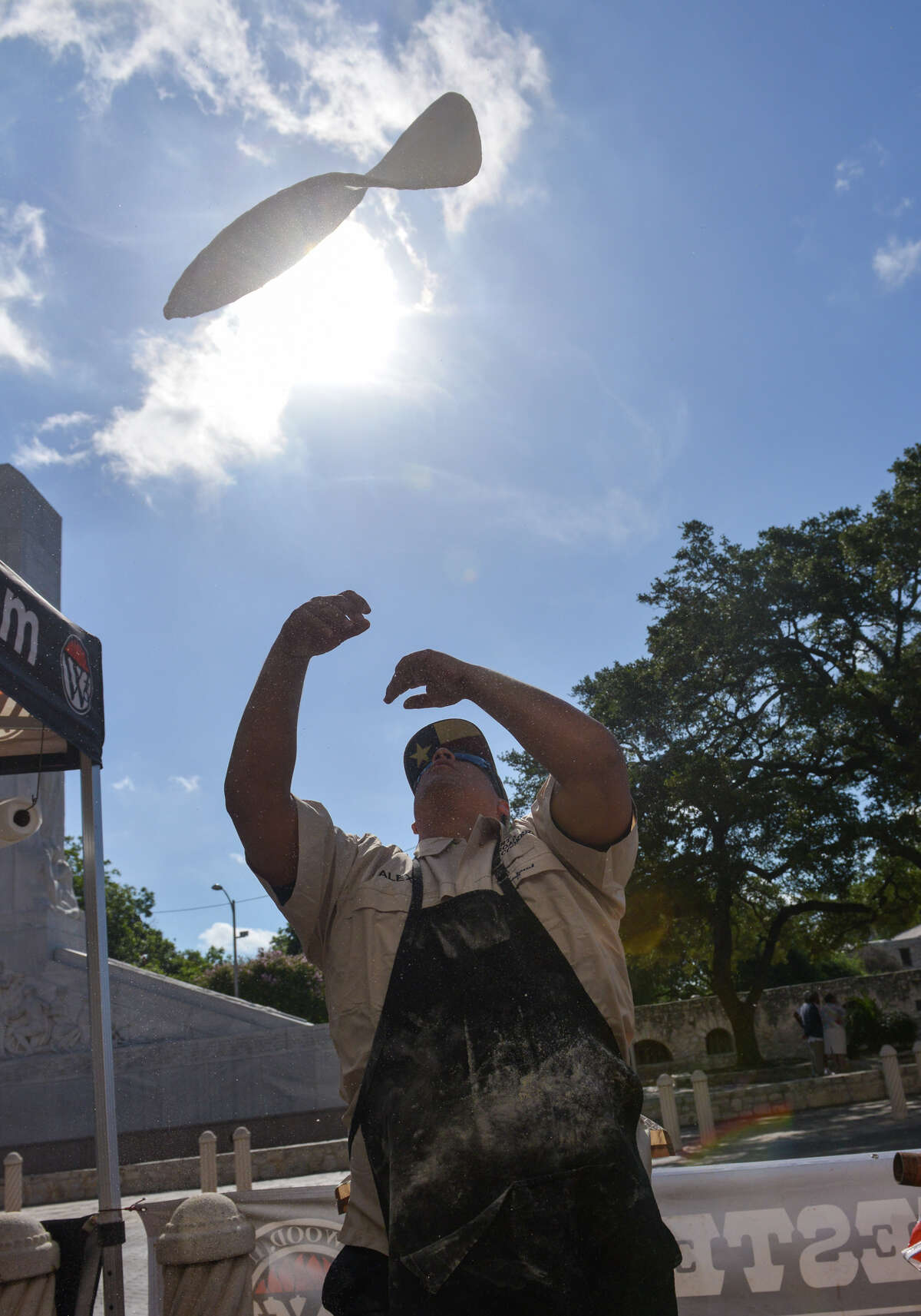 Alex Rymers of Dirt Road Cookers tosses dough in front of the Guinness museum during an attempt to snag the Guinness World Record for the