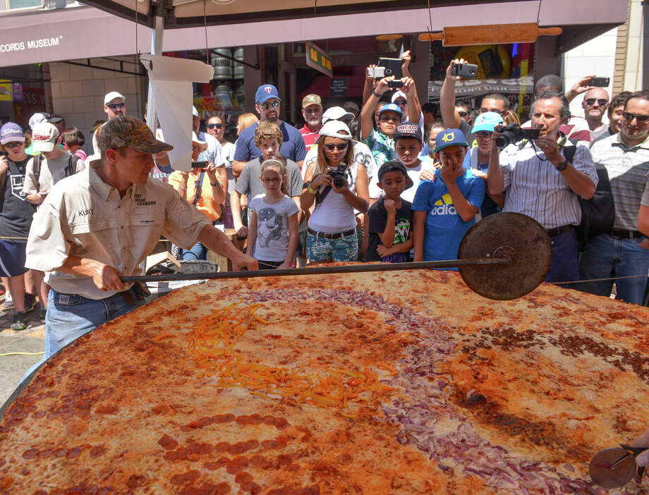"Kurt Oefinger of Dirt Road Cookers cuts the ""largest commercially available"" pizza during the Guinness World Record attempt Aug. 3, 2013, near Alamo Plaza in San Antonio, Texas. The pizza was 92-1/2 inches in diameter and weighed about 88 pounds. Photo: Robin Jerstad, For The San Antonio Express-News"
