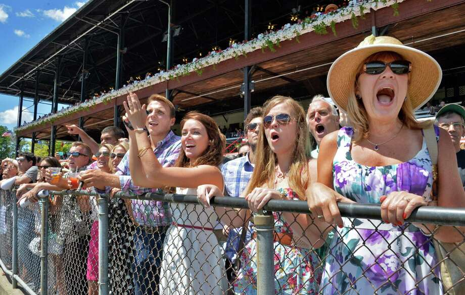 Albee Dailey, left, of Averill Park and Ashley Costello of Easton, Mass., cheer on their winner as Deborah Hartz, at right, and daughter Rachael Hartz's pick loses during the first race at Saratoga Race Course Saturday Aug. 3, 2013, in Saratoga Springs, NY.   (John Carl D'Annibale / Times Union) Photo: John Carl D'Annibale / 10023367A