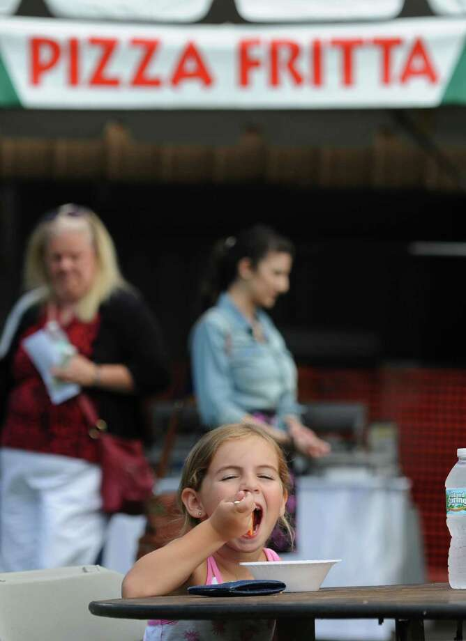 Kaelin Garabo, 5, of Danbury, eats a meatball at the Danbury Italian Festival at the Amerigo Vespucci Lodge in Danbury, Conn. on Saturday, August 3, 2013.  The three-day festival featured authentic Italian food, music and rides for children.  There was also a special 9/11 display with artifacts and memorabilia from the Twin Towers with donations going to the Wounded Warriors Project. Photo: Tyler Sizemore / The News-Times