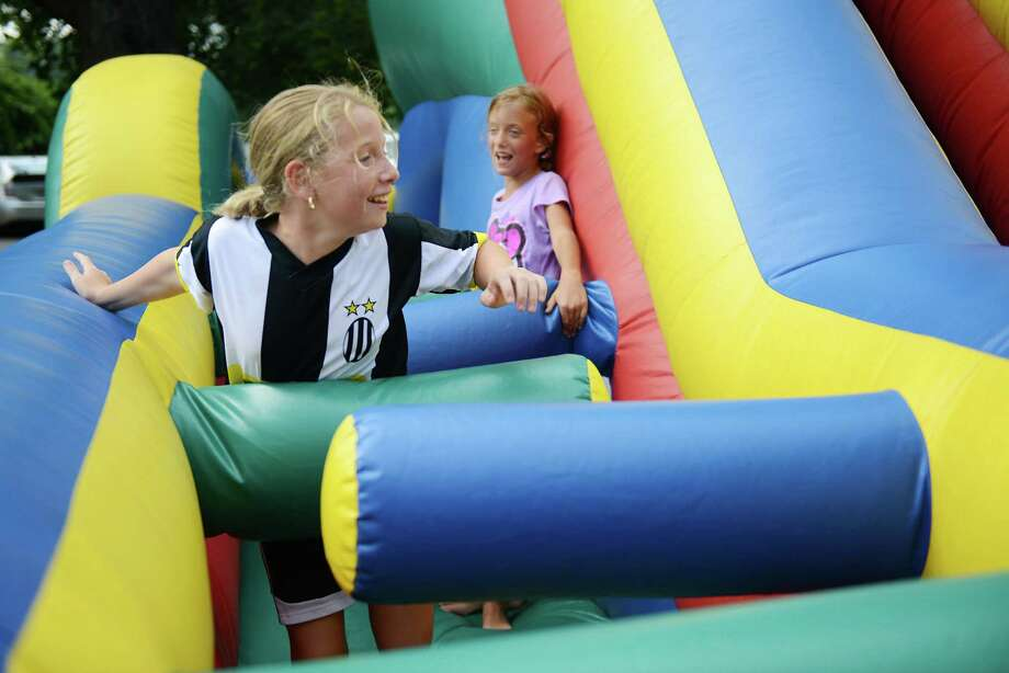 Martina Garofalo, left, 9, of Rocky Hill, and Alexia Cummings, 9, of Moore, Okla., play tag on the bounce house slide at the Danbury Italian Festival at the Amerigo Vespucci Lodge in Danbury, Conn. on Saturday, August 3, 2013.  The three-day festival featured authentic Italian food, music and rides for children.  There was also a special 9/11 display with artifacts and memorabilia from the Twin Towers with donations going to the Wounded Warriors Project. Photo: Tyler Sizemore / The News-Times