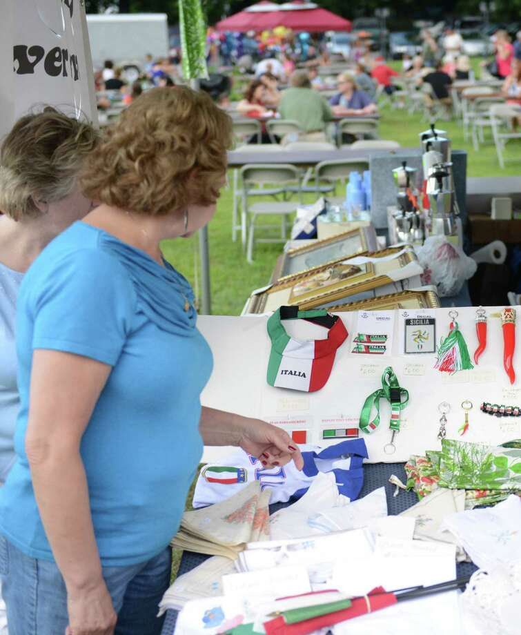 Nancy Coppolo, left, of Danbury, and Joann Lawlor, of Bethel, look at the Gemelli Italian Gifts stand at the Danbury Italian Festival at the Amerigo Vespucci Lodge in Danbury, Conn. on Saturday, August 3, 2013.  The three-day festival featured authentic Italian food, music and rides for children.  There was also a special 9/11 display with artifacts and memorabilia from the Twin Towers with donations going to the Wounded Warriors Project. Photo: Tyler Sizemore / The News-Times