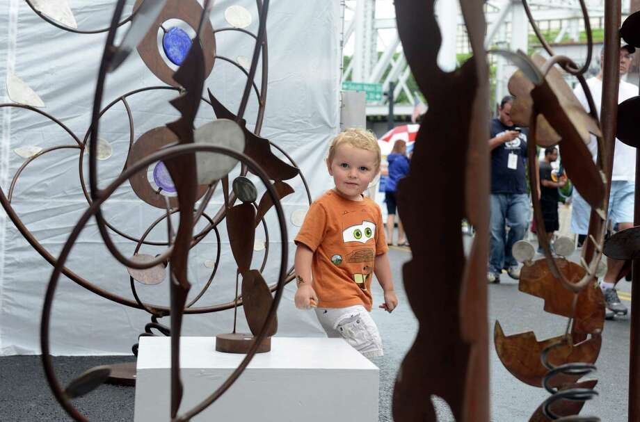 Carl James Sgritta, 2, of Norwalk, checks out sculptures by Whitmore Boogaerts during the 38th annual SoNo Arts Celebration Saturday, Aug. 3, 2013 in Norwalk's Historic District at S. Main and Washington streets. Photo: Autumn Driscoll / Connecticut Post