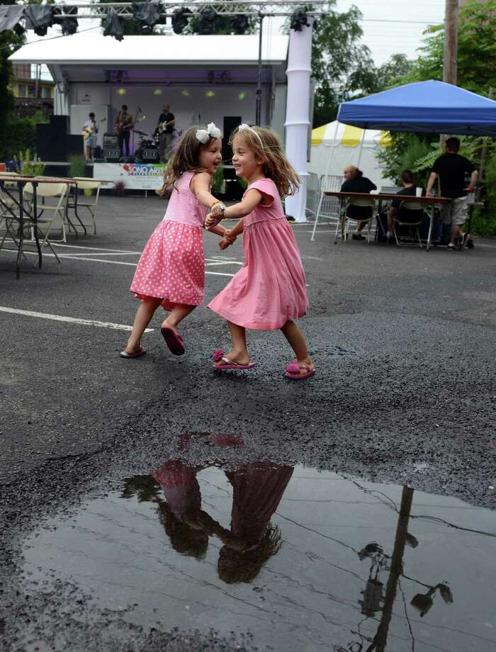 Five-year-old sisters Ellery, left, and Caroline Worst, of Wilton, dance together during the 38th annual SoNo Arts Celebration Saturday, Aug. 3, 2013 in Norwalk's Historic District at S. Main and Washington streets. Photo: Autumn Driscoll / Connecticut Post