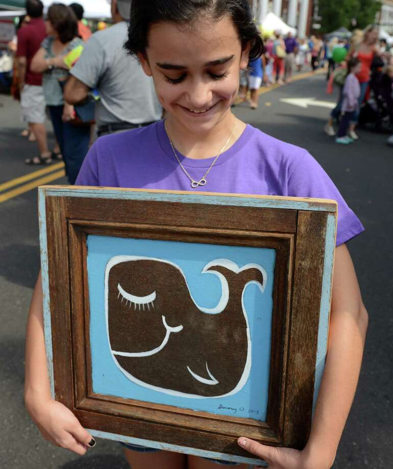 "Emily Lobosco, 12, of Tampa Fla., visiting family in Norwalk, carries her newly purchased painting, by artist Daniel ""Danny O"" O'Connor, during the 38th annual SoNo Arts Celebration Saturday, Aug. 3, 2013 in Norwalk's Historic District at S. Main and Washington streets. Photo: Autumn Driscoll / Connecticut Post"