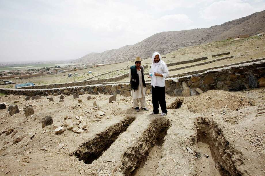 Khwaja Naqib Ahmad, right, and Ghulam Sarwar at a graveyard where unclaimed dead and suicide bombers are buried in Kabul, Afghanistan. Ahmad's job as a municipal gravedigger exacts an emotional toll. Photo: CHRISTOPH BANGERT, STR / NYTNS