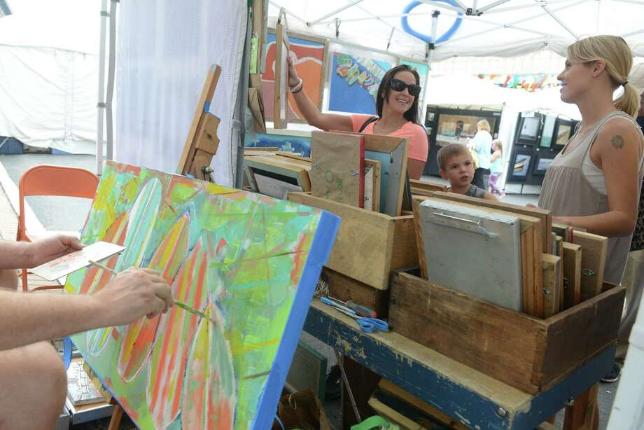 "Artist Daniel ""Danny O"" O'Connor works on a new piece as Erin Bryant, of Brookfield, and Sarah Linder, of Newtown, look at some of his work during the 38th annual SoNo Arts Celebration Saturday, Aug. 3, 2013 in Norwalk's Historic District at S. Main and Washington streets. Photo: Autumn Driscoll / Connecticut Post"