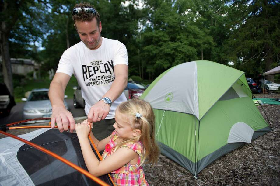 Isla Freshwater, 5, helps her father, Guy, set up their tent during the annual family campout at Stamford Museum and Nature Center on Saturday, August 3, 2013. Photo: Lindsay Perry / Stamford Advocate