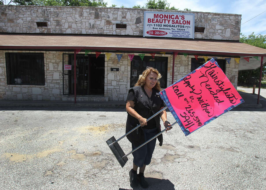 Monica Prater places a help-wanted sign in front of her new hair salon in a former thrift store on Nogalitos Street. She'd originally gone to her personal bank, which — wary of her lack of business experience — rejected her loan request. Photo: JOHN DAVENPORT, SAN ANTONIO EXPRESS-NEWS / ©San Antonio Express-News/Photo may be sold to the public