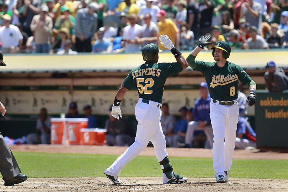 A's Yoenis Cespedes, (52) drives in Jed Lowrie, (8) with a two run home run in the first inning, as the Oakland Athletics take on the Texas Rangers at O.co Coliseum in Oakland, Calif.,  on Saturday August 3, 2013,. Photo: Michael Macor, San Francisco Chronicle
