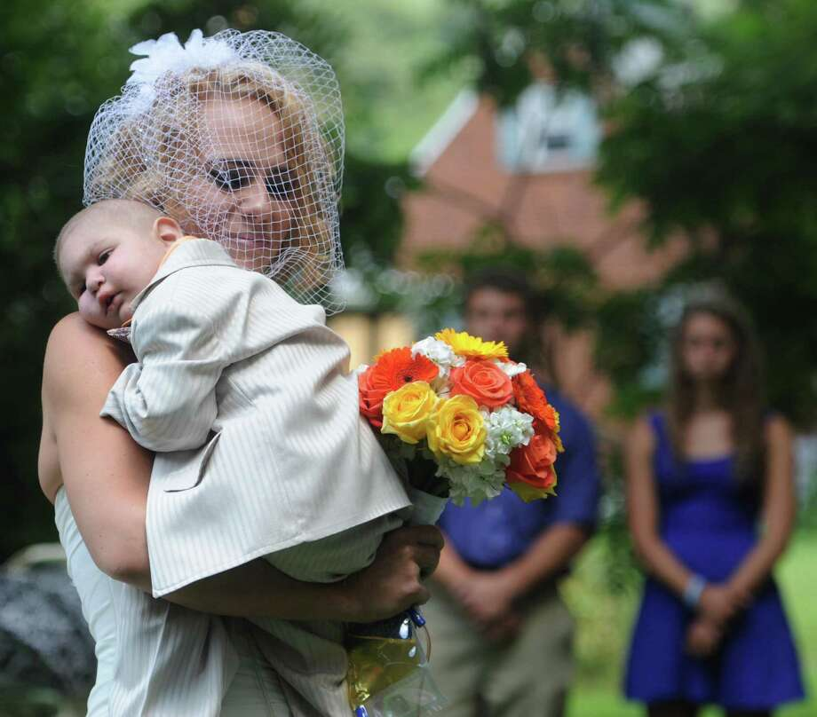 Christine Swidorsky carries her son and the couple's best man, Logan Stevenson, 2, down the aisle to her husband-to-be Sean Stevenson during the wedding ceremony on Saturday, Aug. 3, 2013 in Jeannette, Pa.  Logan stood with his grandmother, Debbie Stevenson, during a 12-minute ceremony uniting Logan's mother and his father. The boy has leukemia and other complications.  The Stevensons abandoned an original wedding date of July 2014 after learning from doctors late last month that their son had two to three weeks to live. The couple wanted Logan to see them marry and to be part of family photos. Logan, who was born Oct. 22, 2010, was diagnosed shortly after his first birthday with acute myeloid leukemia. He has Fanconi anemia, a rare disease that often leads to cancer. Photo: Eric Schmadel, Associated Press / Tribune Review