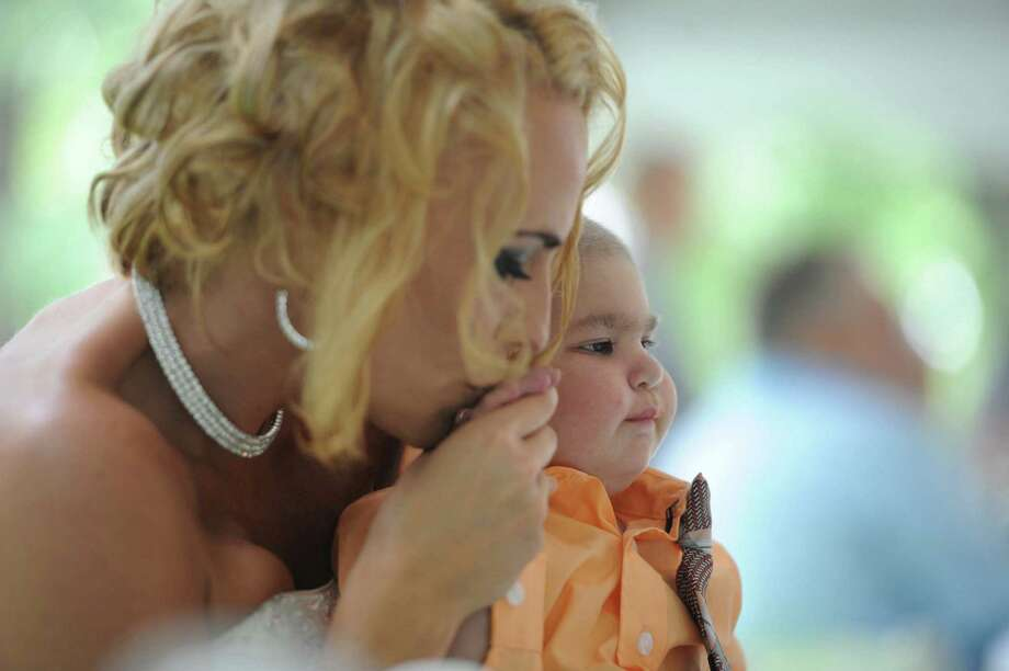 Newlywed Christine Stevenson kisses the hand of her son, Logan Stevenson, 2, after marrying Sean Stevenson in a wedding ceremony on Saturday, Aug. 3, 2013 in Jeannette, Pa. Photo: Eric Schmadel, Associated Press / Tribune Review