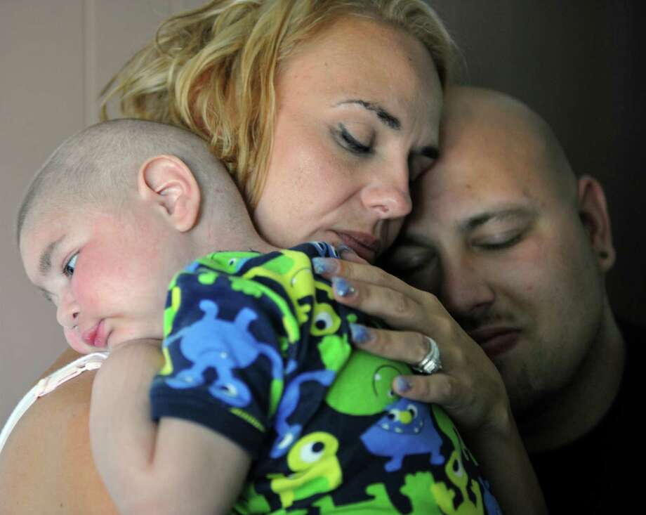 Christine Swidorsky holds her son, Logan Stevenson, 2, with her husband-to-be and Logan's father Sean Stevenson, for a portrait on Tuesday, July 30, 2013 in their Jeannette, Pa., home. The Pennsylvania couple plans to have their dying toddler serve as the groom's best man when they wed on Saturday, Aug. 3. The couple had planned to wed next year, but decided to move the ceremony up to Saturday so the boy, who has leukemia and other complications, could participate. Logan has Fanconi anemia, a rare disease that often results in cancer. Doctors last week gave the boy two to three weeks to live. Photo: Eric Schmadel, Associated Press / Tribune-Review