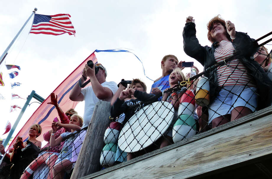 Family and friends cheer on swimmers as they arrive at the dock, during St. Vincent's Swim Across the Sound Marathon at Captain's Cove Seaport in Bridgeport, Conn. on Saturday August 3, 2013. Photo: Christian Abraham / Connecticut Post