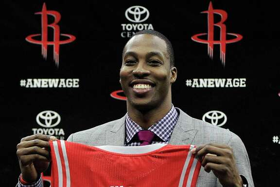 Dwight Howard holds his Houston Rocket's jersey during the press conference and welcoming ceremony for him at the Toyota Center, Saturday, July 13, 2013, in Houston. (AP Photo/Houston Chronicle, Karen Warren)
