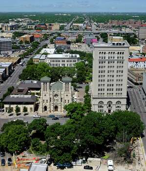 The San Antonio skyline is seen — including San Fernando Cathedral (left), Municipal Plaza Building (right) and City Hall (behind San Fernando) — May 11, 2007, from the roof-top pool of the Drury Plaza hotel, which is in the former Alamo National Bank Building. Photo: William Luther, San Antonio Express-News / SAN ANTONIO EXPRESS-NEWS