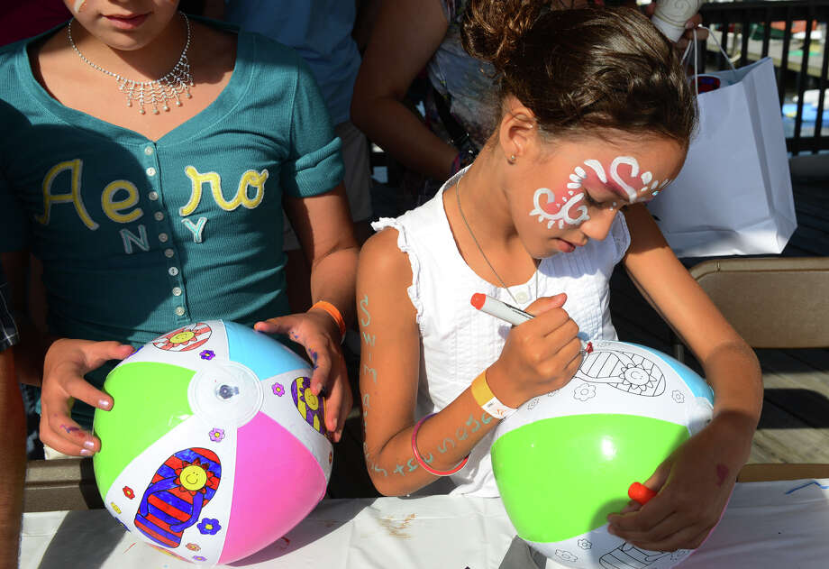 Elyssa Torres, 8, of Stratford, decorates her beach ball, during activities at the St. Vincent's Swim Across the Sound Marathon at Captain's Cove Seaport in Bridgeport, Conn. on Saturday August 3, 2013. Photo: Christian Abraham / Connecticut Post