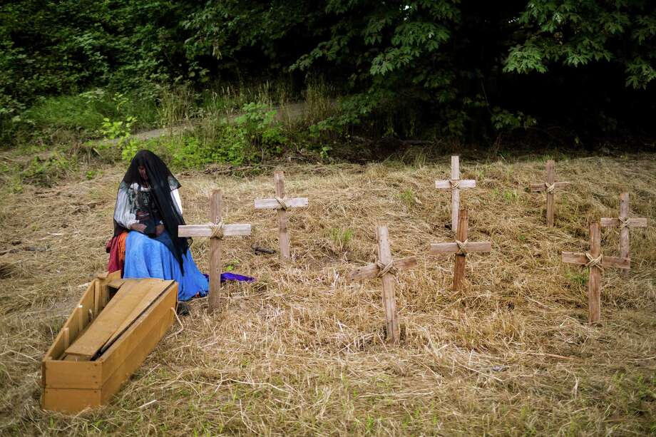 Eleven-year event employee Mary Osborn-Dixon, of Maui, grieves over a coffin and a collection of cross-adorned graves at The Washington Midsummer Renaissance Faire Saturday, August 3, 2013, at The Kelley Farm in Bonney Lake. The event continues August 10-11 and 17-18. Photo: JORDAN STEAD, SEATTLEPI.COM / SEATTLEPI.COM