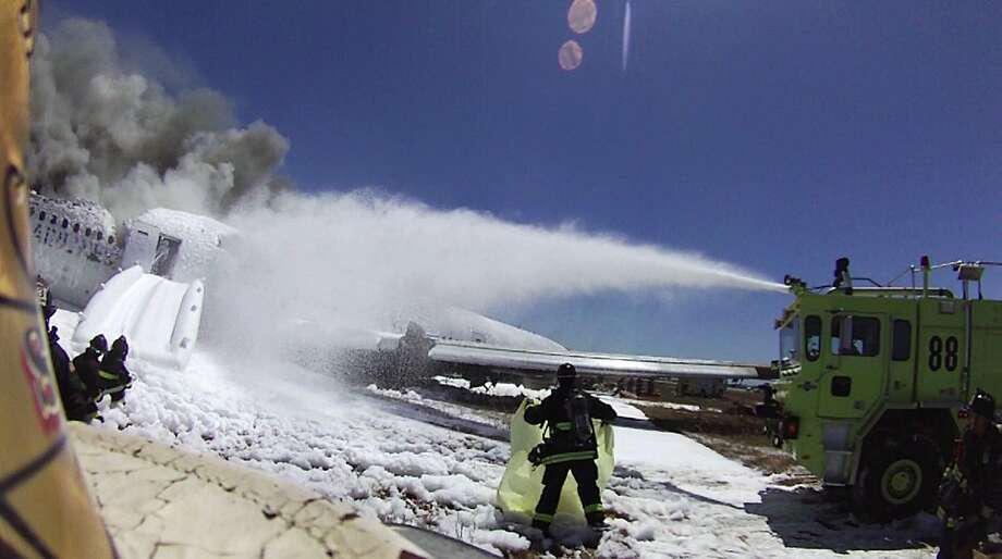An image from the helmet-mounted video camera of a San Francisco fire battalion chief at the scene of the crash of Asiana Flight 214 shows a firefighter covering the body of passenger Ye Meng Yuan at San Francisco International Airport on July 6, 2013 in San Francisco, California.