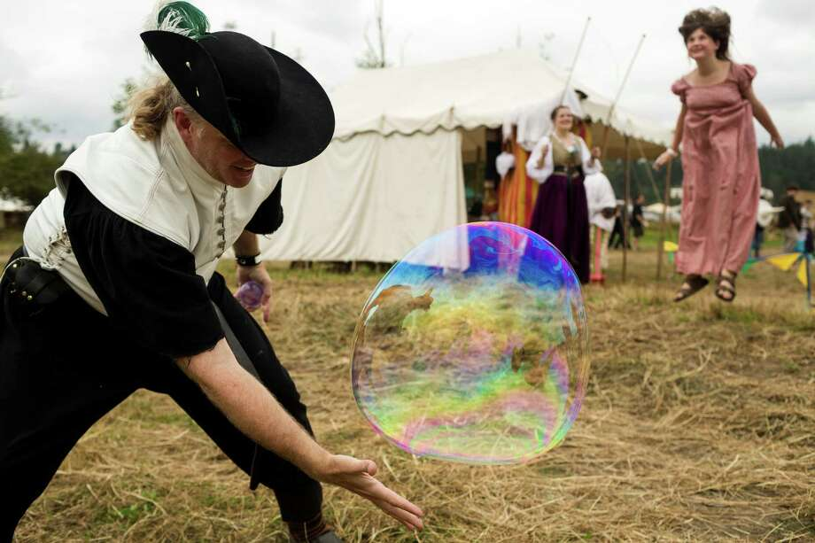 Richard Bailey, left, reaches for a bubble as Abbie Fulon, 13, right, pops one with her head during The Washington Midsummer Renaissance Faire Saturday, August 3, 2013, at The Kelley Farm in Bonney Lake. The event continues August 10-11 and 17-18. Photo: JORDAN STEAD, SEATTLEPI.COM / SEATTLEPI.COM