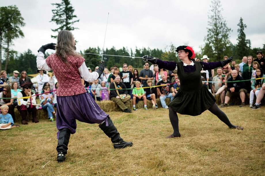 Onlookers watch a fencing and arms demonstration by an Italian and Frenchman pair during The Washington Midsummer Renaissance Faire Saturday, August 3, 2013, at The Kelley Farm in Bonney Lake. The event continues August 10-11 and 17-18. Photo: JORDAN STEAD, SEATTLEPI.COM / SEATTLEPI.COM
