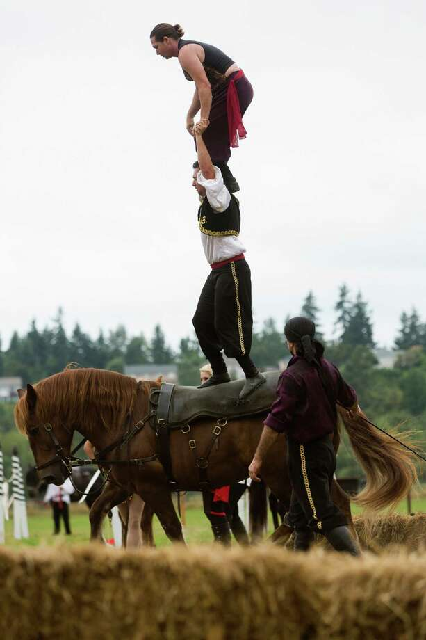 Riders from the Ma'Ceo Gypsy Horse Extravaganza presented by Cavallo Equestrian Arts clamber on top of each other and their steed during The Washington Midsummer Renaissance Faire Saturday, August 3, 2013, at The Kelley Farm in Bonney Lake. The event continues August 10-11 and 17-18. Photo: JORDAN STEAD, SEATTLEPI.COM / SEATTLEPI.COM