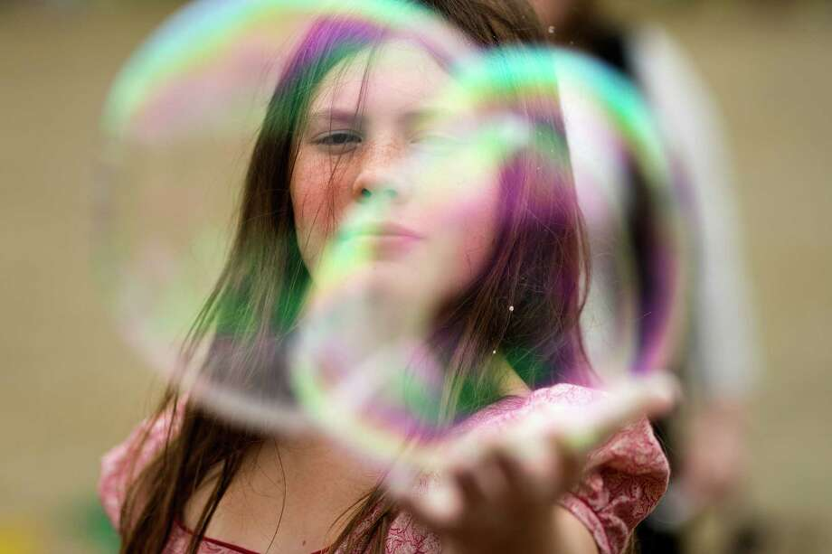 Abbie Fulon, 13, reaches to pop a gigantic bubble during The Washington Midsummer Renaissance Faire Saturday, August 3, 2013, at The Kelley Farm in Bonney Lake. The event continues August 10-11 and 17-18. Photo: JORDAN STEAD, SEATTLEPI.COM / SEATTLEPI.COM