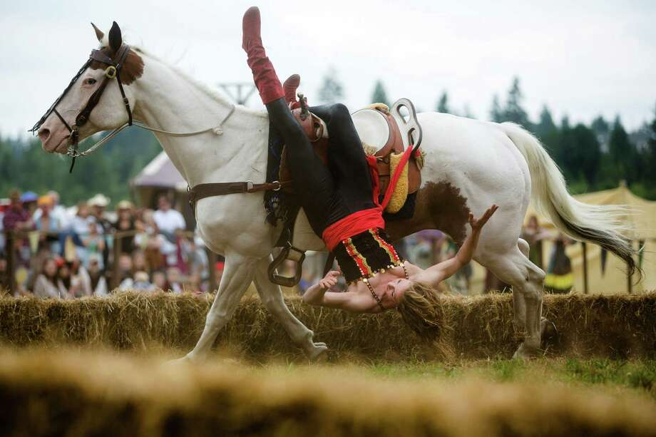 A rider from the Ma'Ceo Gypsy Horse Extravaganza presented by Cavallo Equestrian Arts dangles from her steed during The Washington Midsummer Renaissance Faire Saturday, August 3, 2013, at The Kelley Farm in Bonney Lake. The event continues August 10-11 and 17-18. Photo: JORDAN STEAD, SEATTLEPI.COM / SEATTLEPI.COM