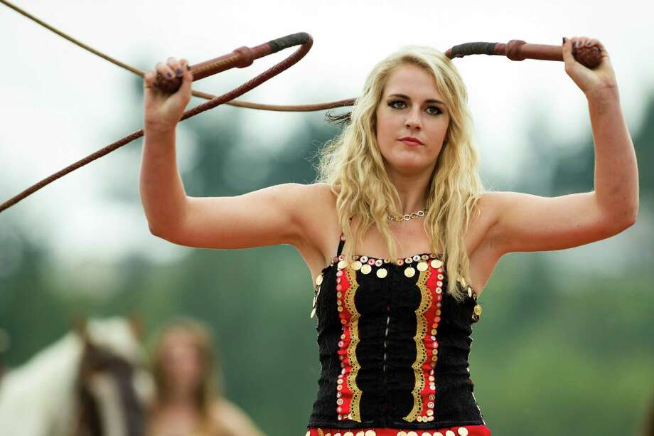 A whip-wielding member from the Ma'Ceo Gypsy Horse Extravaganza presented by Cavallo Equestrian Arts cracks her weapons at onlookers during The Washington Midsummer Renaissance Faire Saturday, August 3, 2013, at The Kelley Farm in Bonney Lake. The event continues August 10-11 and 17-18. Photo: JORDAN STEAD, SEATTLEPI.COM / SEATTLEPI.COM