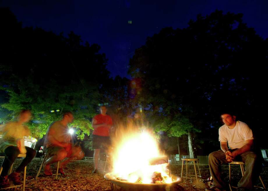 Campers gather around the fire pit to roast marshmallows and make s'mores during the annual family campout at Stamford Museum and Nature Center on Saturday, August 3, 2013. Photo: Lindsay Perry / Stamford Advocate
