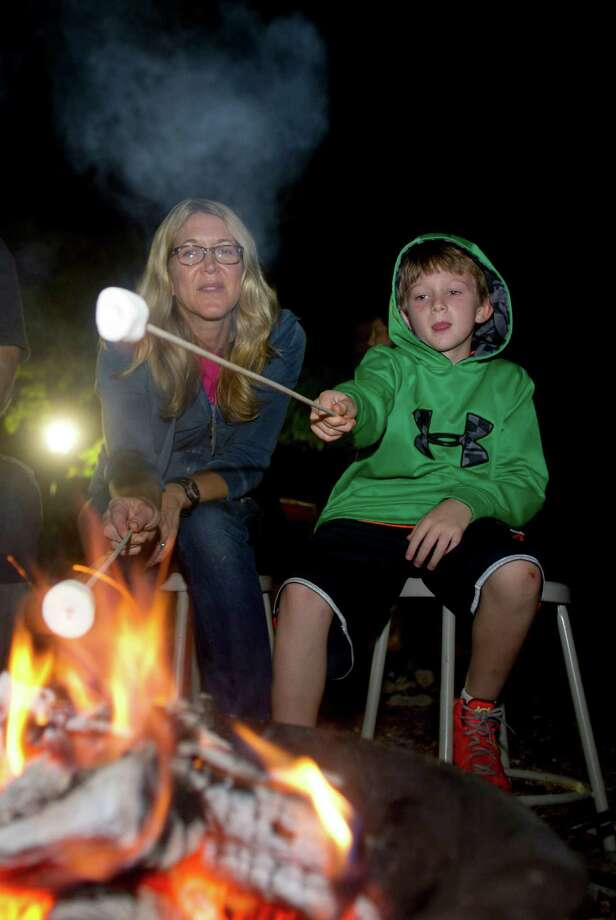 Griffin Bramwit, 7, and his mother, Michelle, gather around the fire pit to roast marshmallows and make s'mores during the annual family campout at Stamford Museum and Nature Center on Saturday, August 3, 2013. Photo: Lindsay Perry / Stamford Advocate