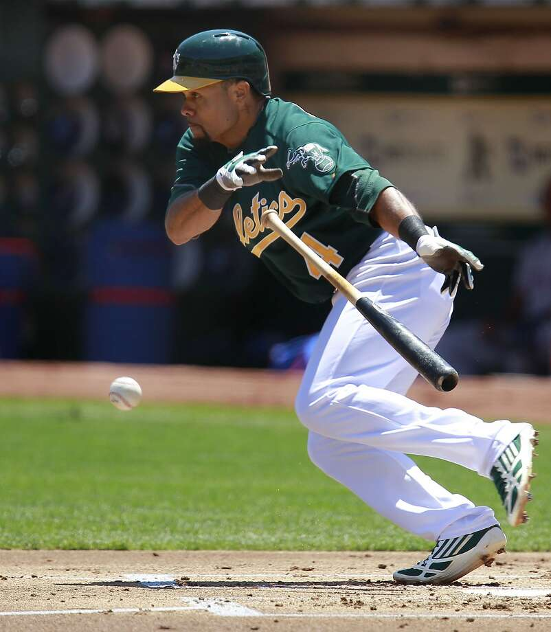 A's Coco Crisp, (4) lays down a bunt single in the first inning, as the Oakland Athletics take on the Texas Rangers at O.co Coliseum in Oakland, Calif.,  on Saturday August 3, 2013,. Photo: Michael Macor, San Francisco Chronicle