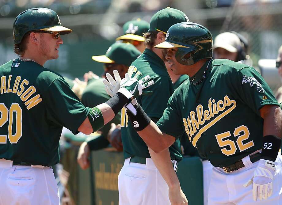 A's Josh Donaldson, (20) celebrates a two run home run by Yoenis Cespedes, (52)  in the first inning, as the Oakland Athletics take on the Texas Rangers at O.co Coliseum in Oakland, Calif.,  on Saturday August 3, 2013,. Photo: Michael Macor, San Francisco Chronicle