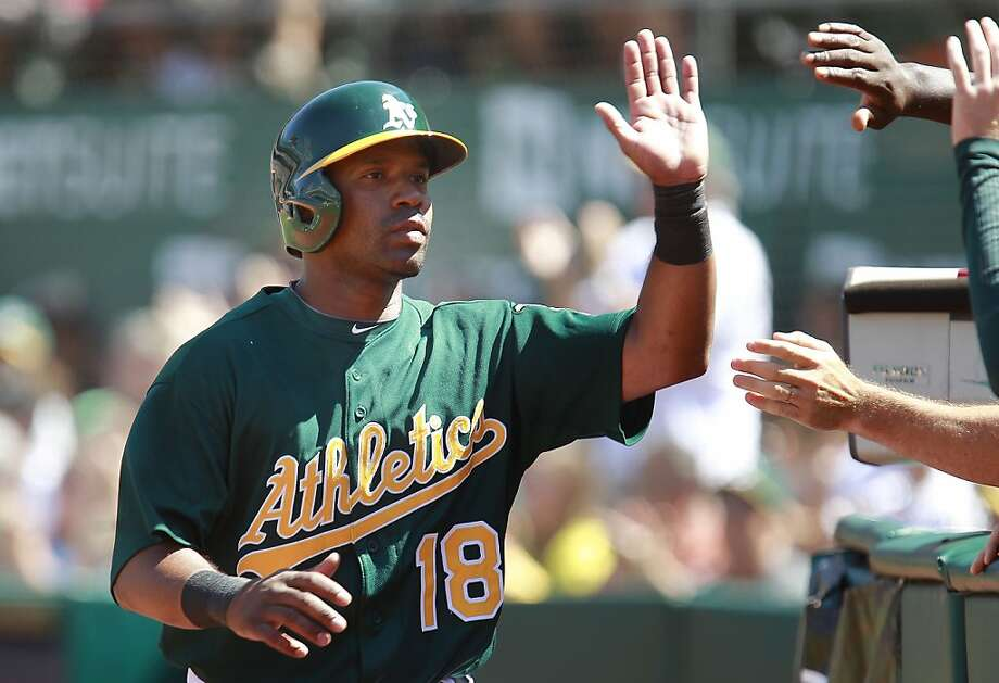 A's Alberto Callaspo, (18) scored a run on a bunt by his teammate Eric Sogard, (28) to give the Oakland Athletics a 4-2 lead in the seventh inning against the Texas Rangers at O.co Coliseum in Oakland, Calif.,  on Saturday August 3, 2013,. Photo: Michael Macor, San Francisco Chronicle
